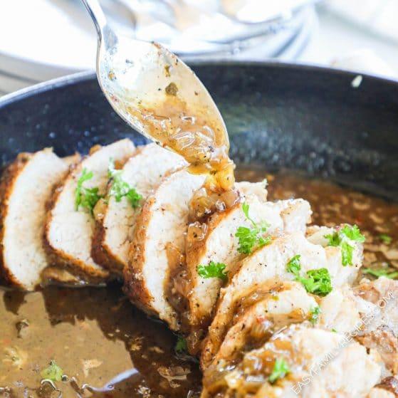 Spooning garlic sauce over pork tenderloin