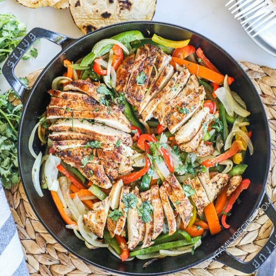 Chicken Fajitas prepared in a cast iron skillet Tex Mex style with onions, peppers, and lime.