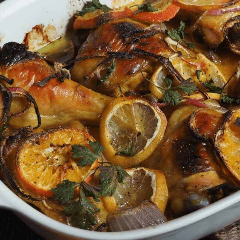 honey roasted chicken in pan with orange slices