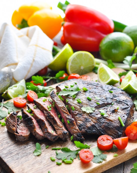 An easy grilled flank steak is transformed into juicy, tender, and flavorful Carne Asada — with just 5 minutes of prep work! Thanks to a simple Latin American-inspired steak marinade, the charred meat is perfect for salads, tacos, burritos and quesadillas.
