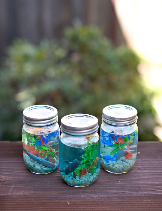 Make Real-Looking Aquariums by adding plants, rocks, and aquarium figurines to a mason jar of blue water.