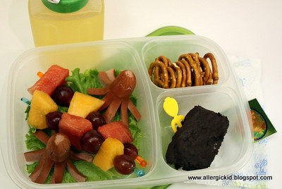 First day of second grade lunchbox - (turkey) octodogs, fruit skewers on swizzle sticks, pretzels and a big chunk o' leftover chocolate birthday cake with a food pick. On the side are the usual apple juice/water mix and a somewhat hidden Tyrannosaurus Rex sticker. Thanks to Libby for this!  http://bit.ly/b0WzrU
