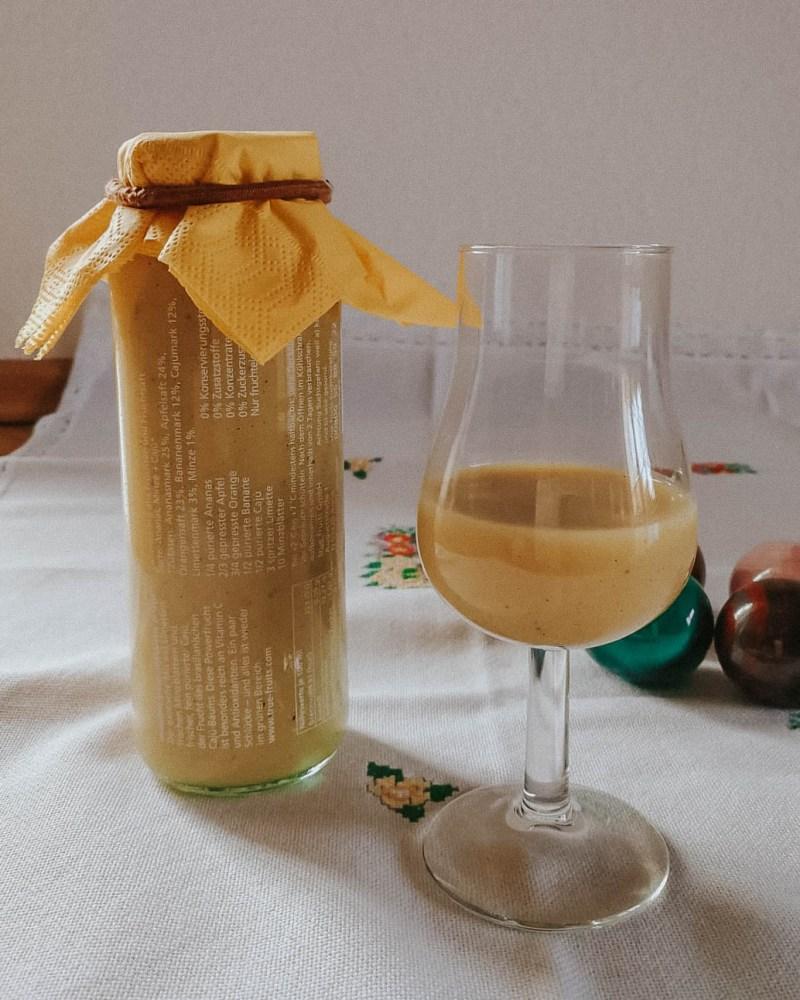 Eierlikör in der Flasche zur Aufbewahrung, davor ein bisschen davon in ein Glas eingeschenkt