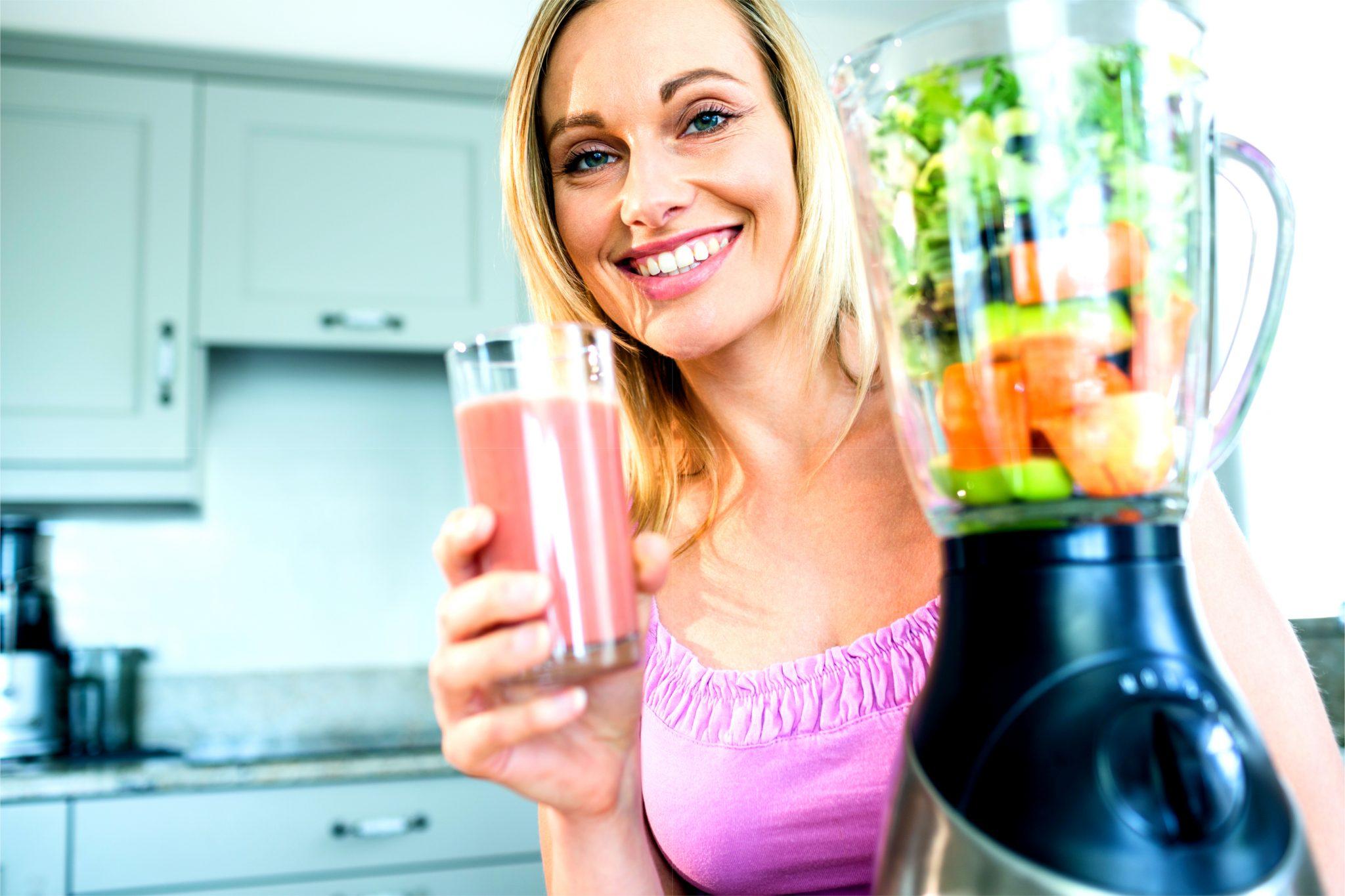 ニンジンジュースをミキサーで作ってる女性