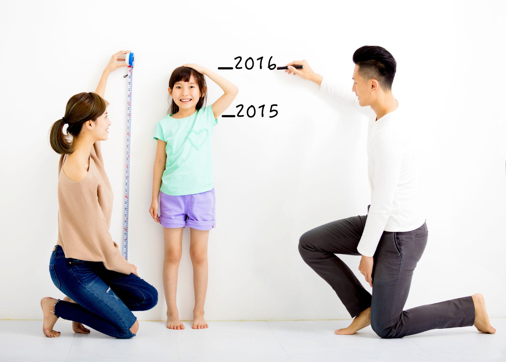両親に身長を記録してもらっている娘
