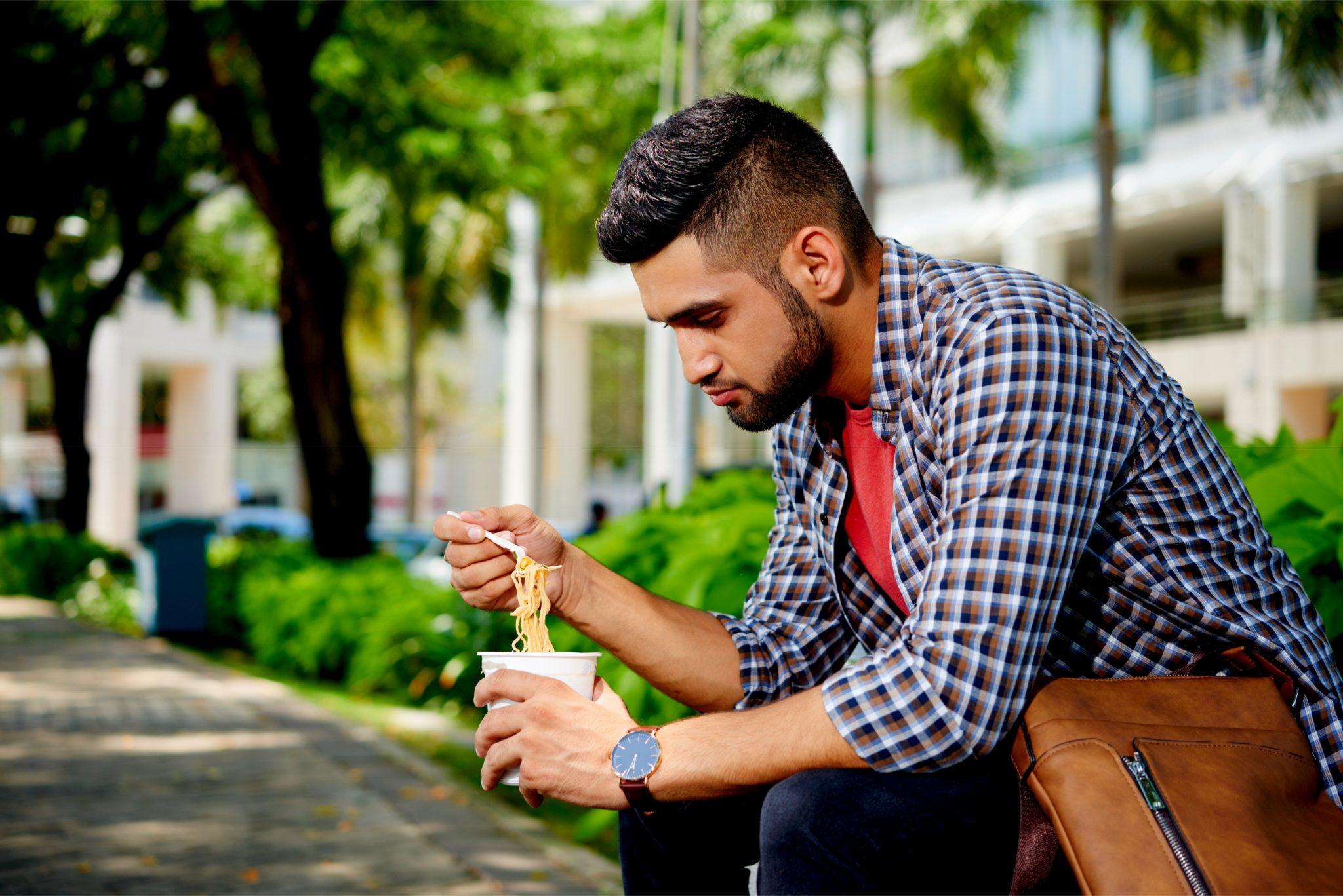 ベンチでカップラーメンを食べている男性