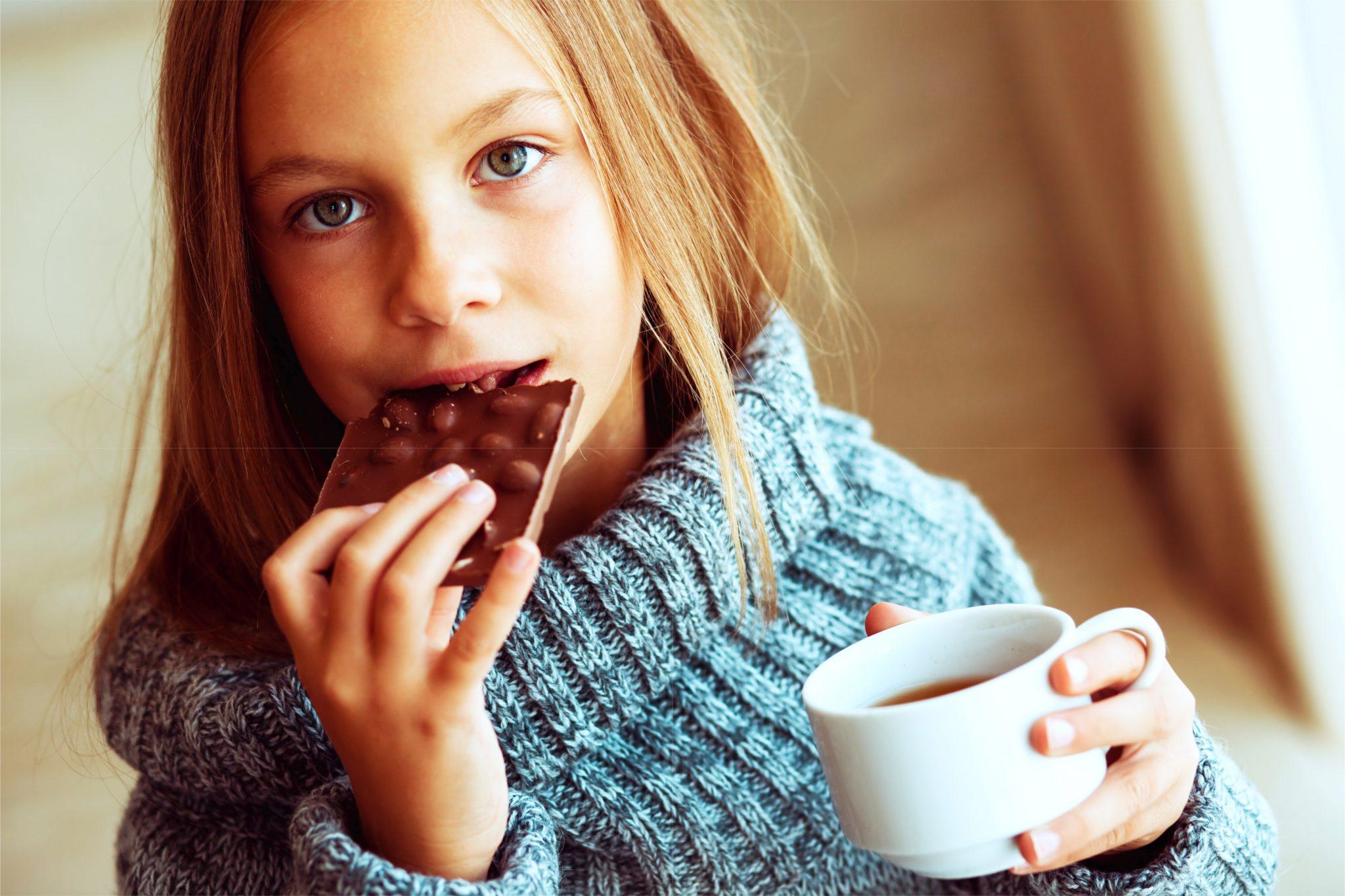 コーヒーを飲みながらチョコを食べている女性