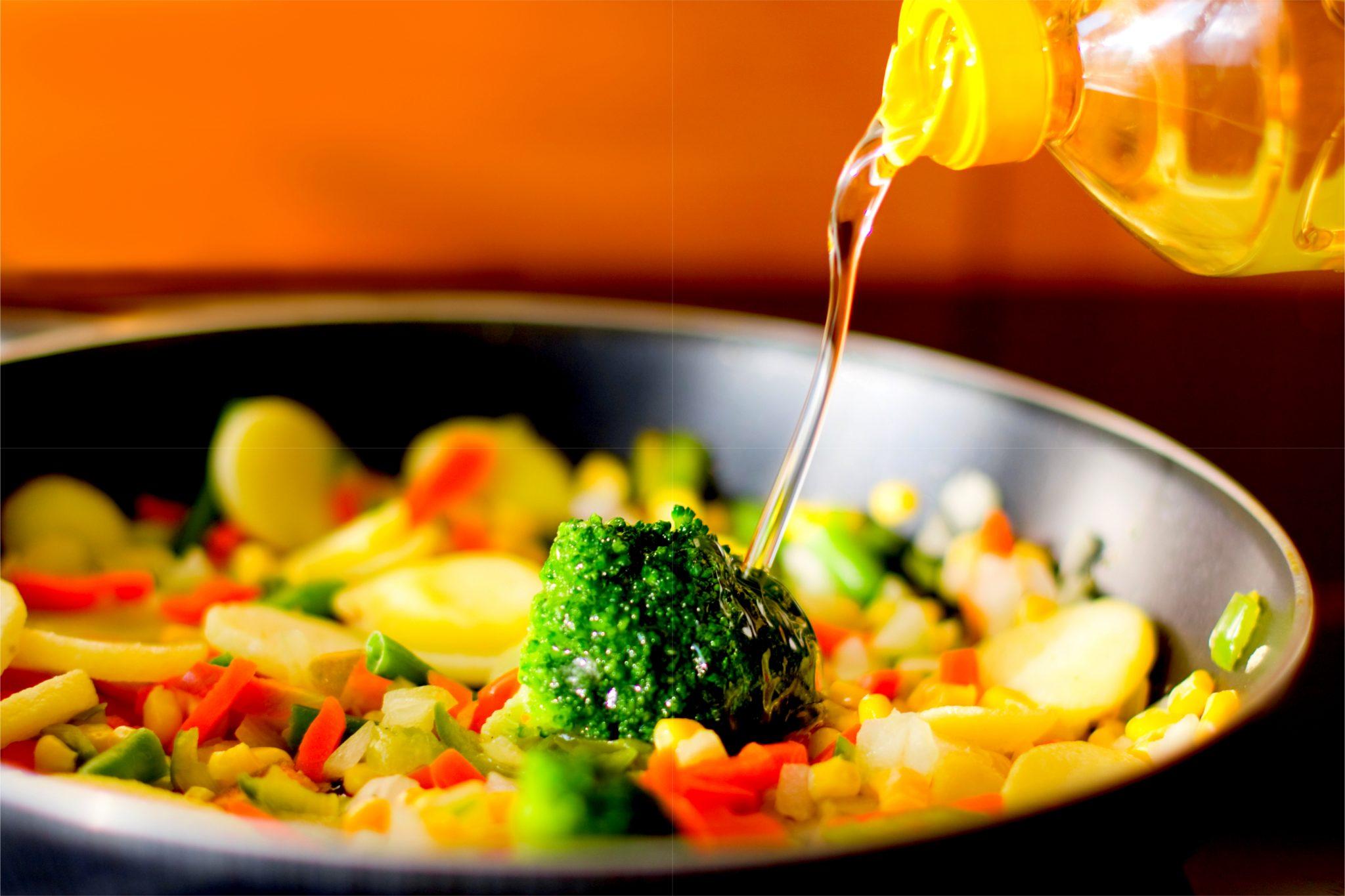野菜炒めに油を注いでいる