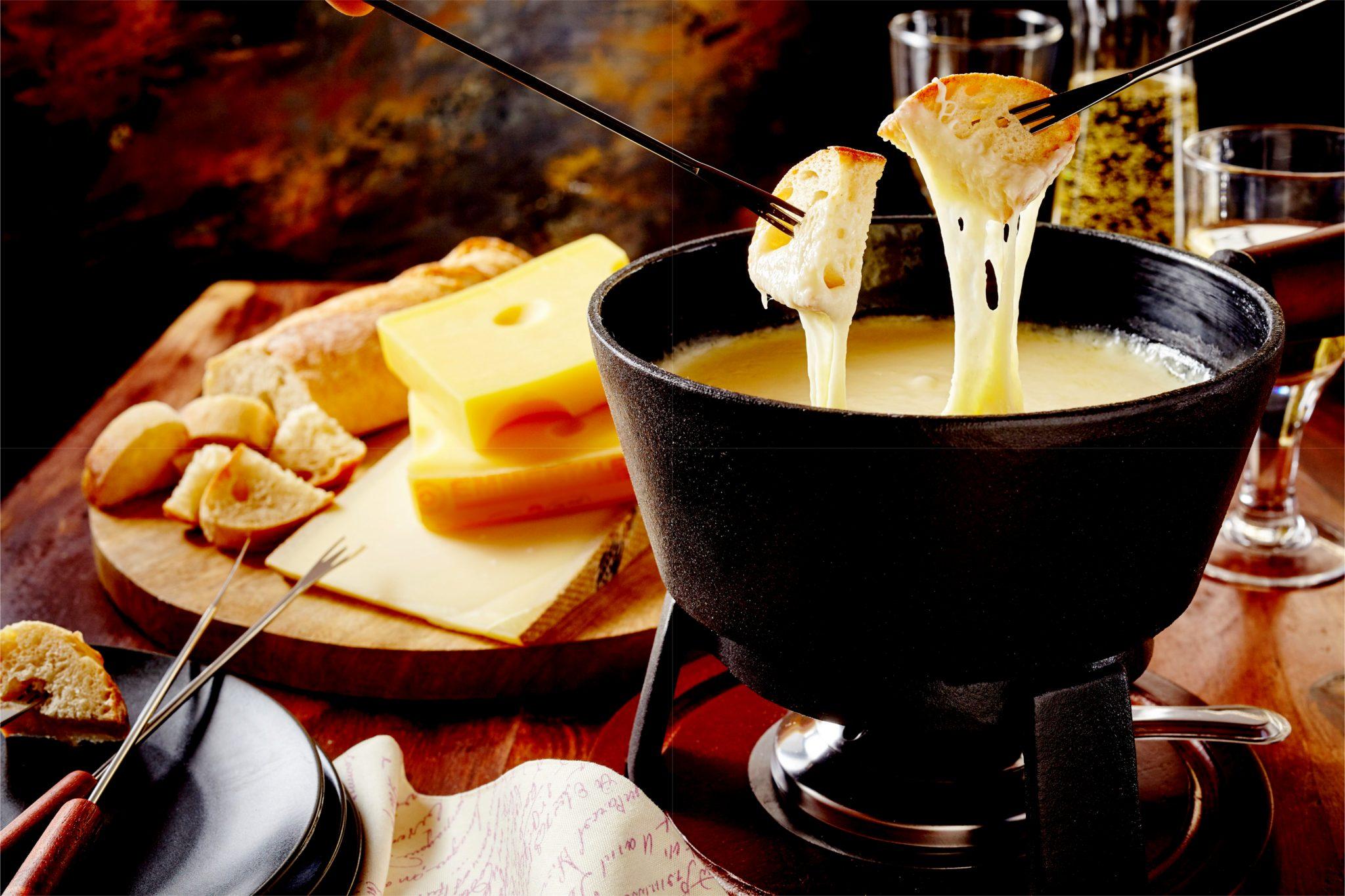 パンをチーズにつけている写真