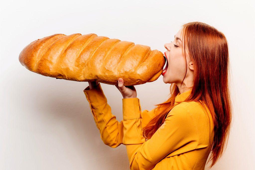 巨大なパンを食べようとしている女性