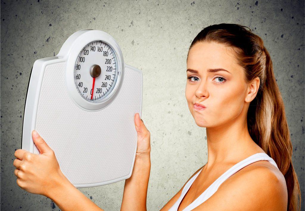 体重計の数値に不満な顔をしている女性