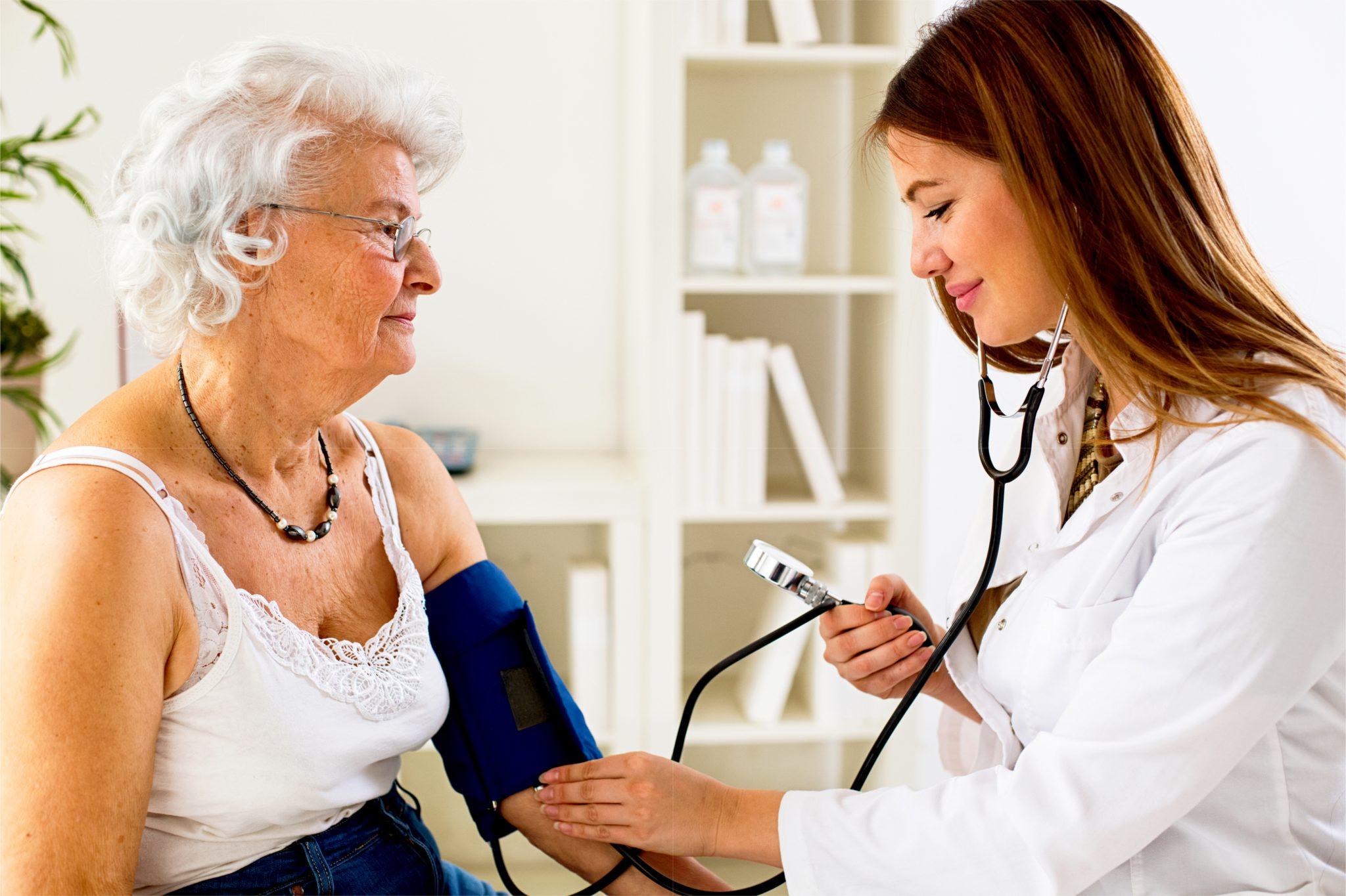 医者が高血圧のあばあちゃんの血圧を計測している
