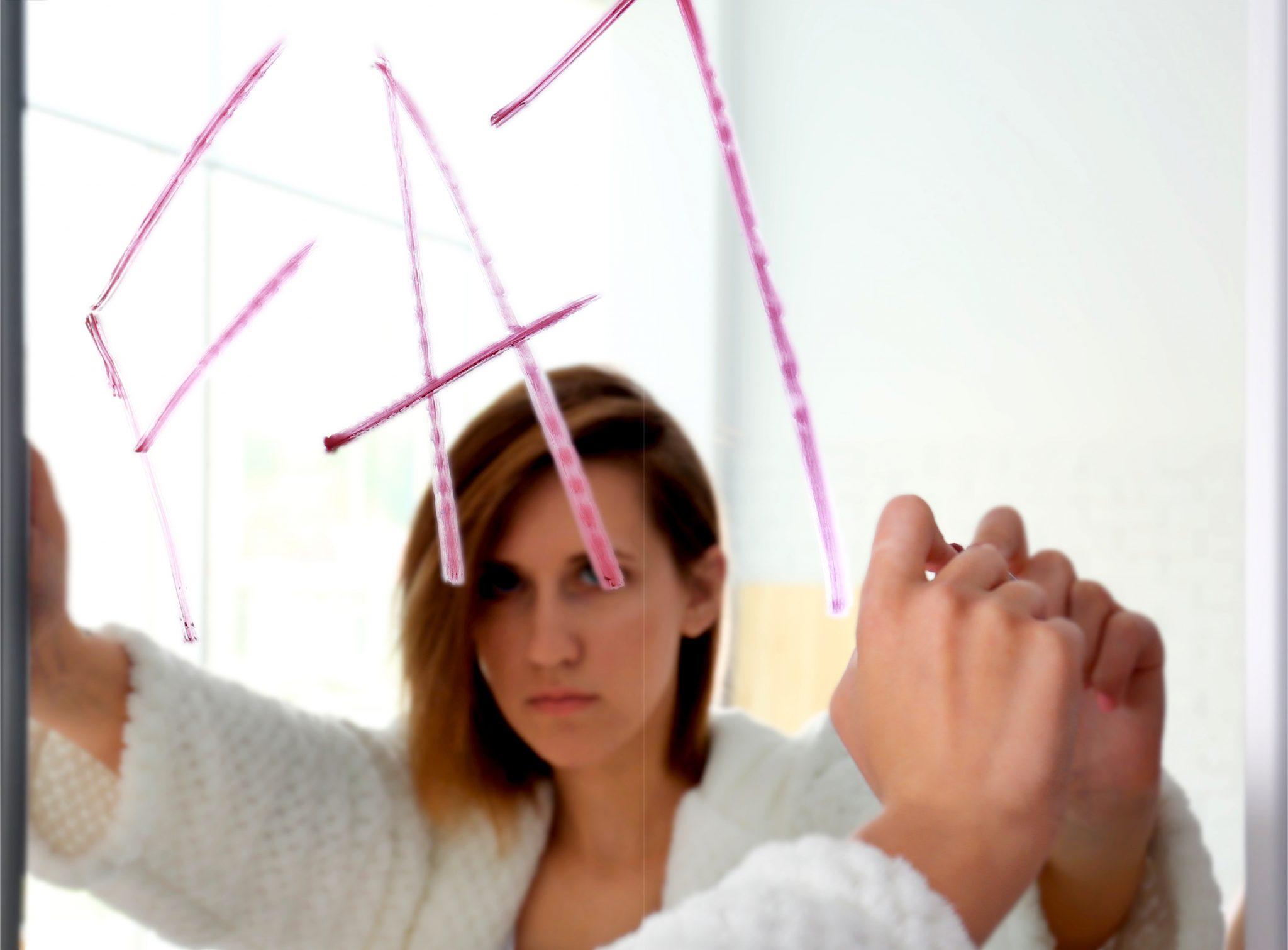 鏡にデブと書いている女性