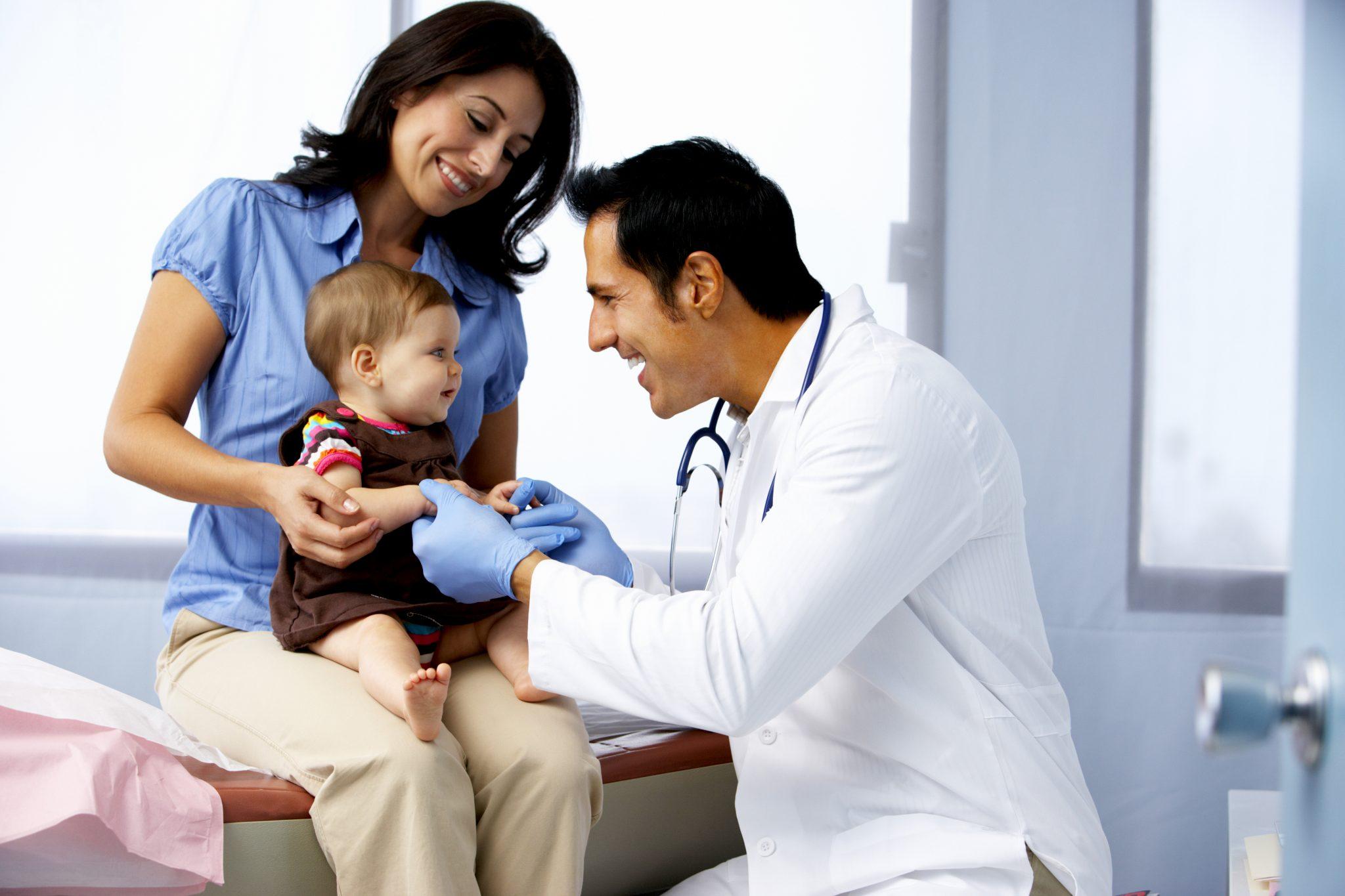 お医者さんに子どもを健診してもらっている