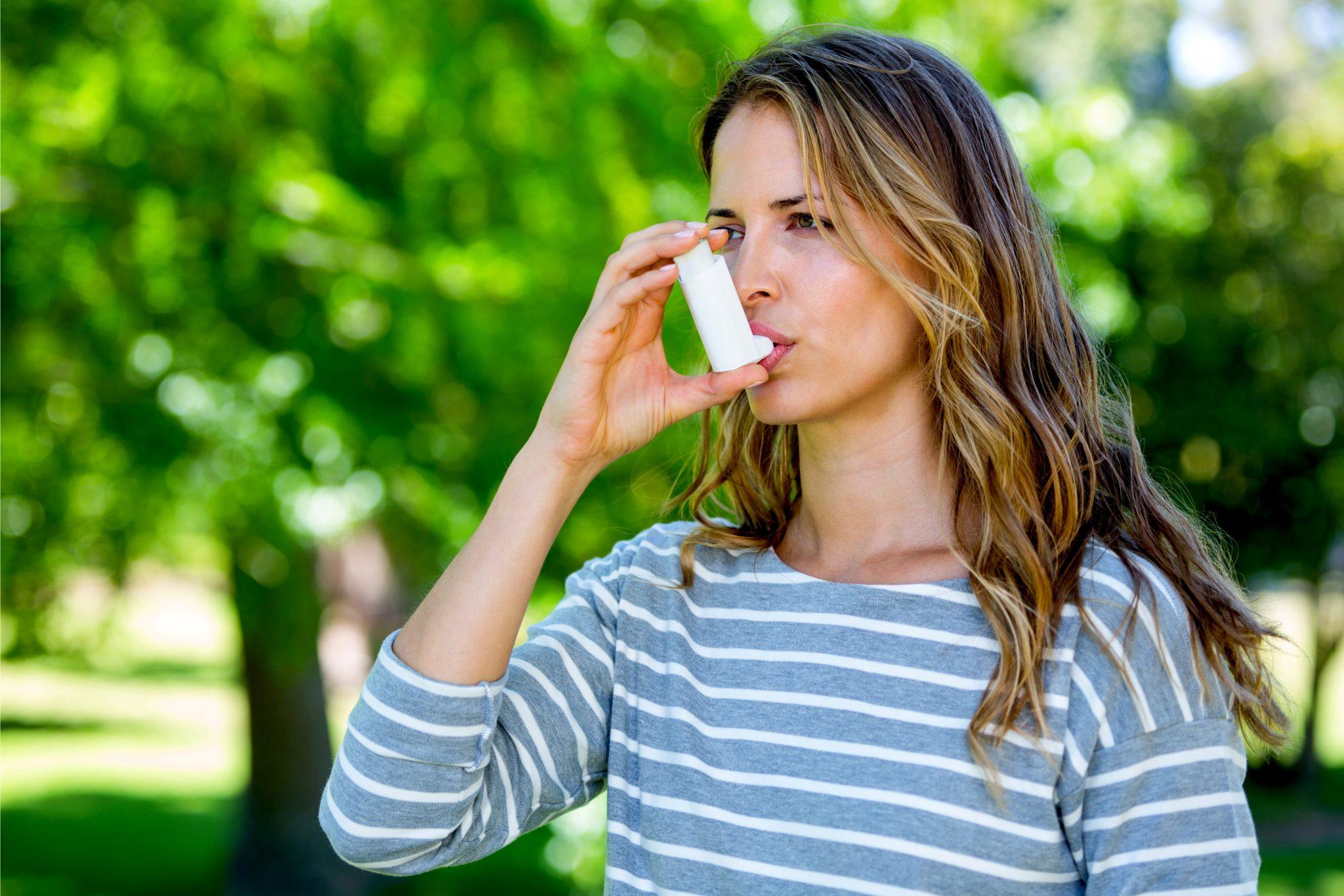 喘息の吸引器具を使っている女性