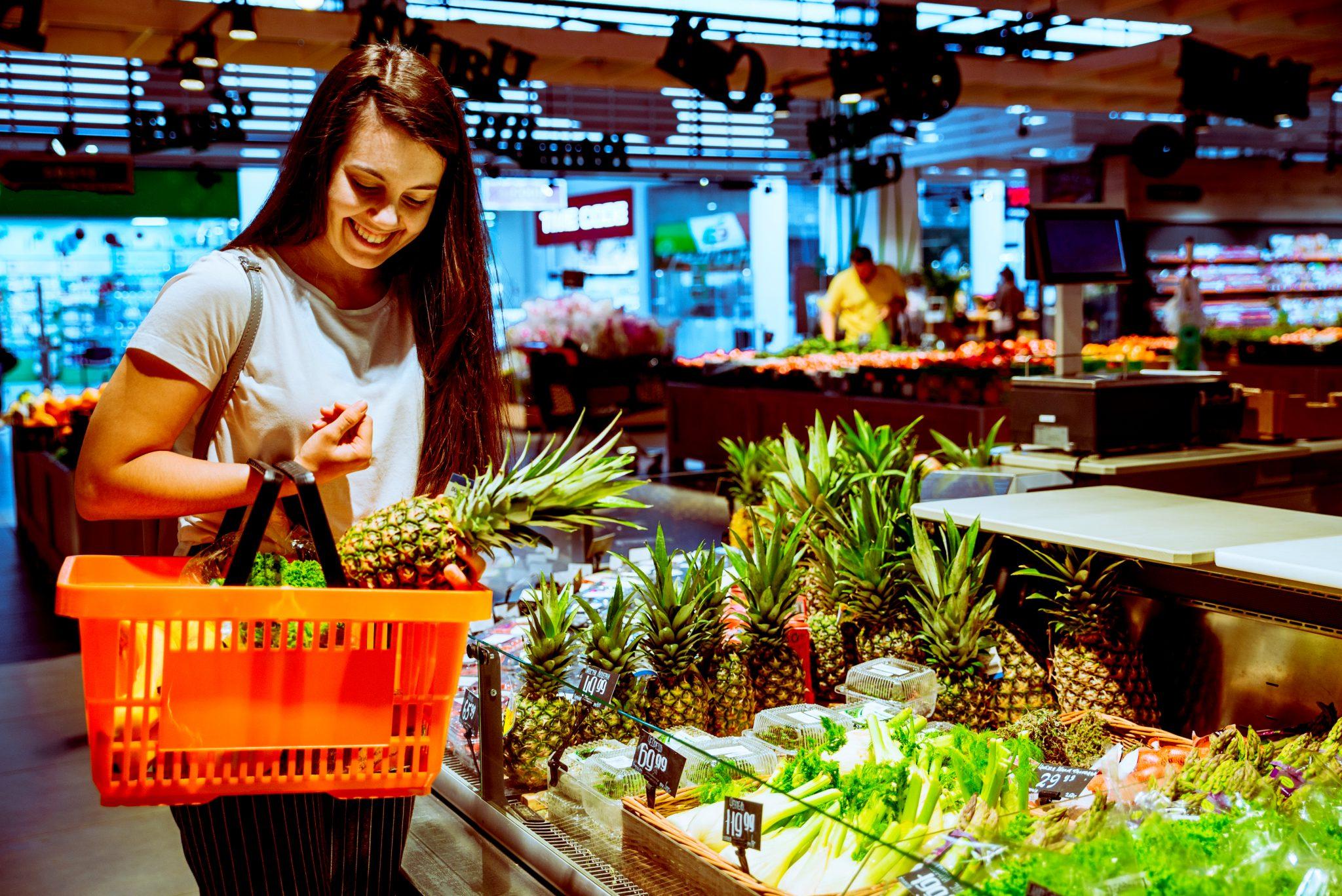 パイナップルをスーパーで買っている女性