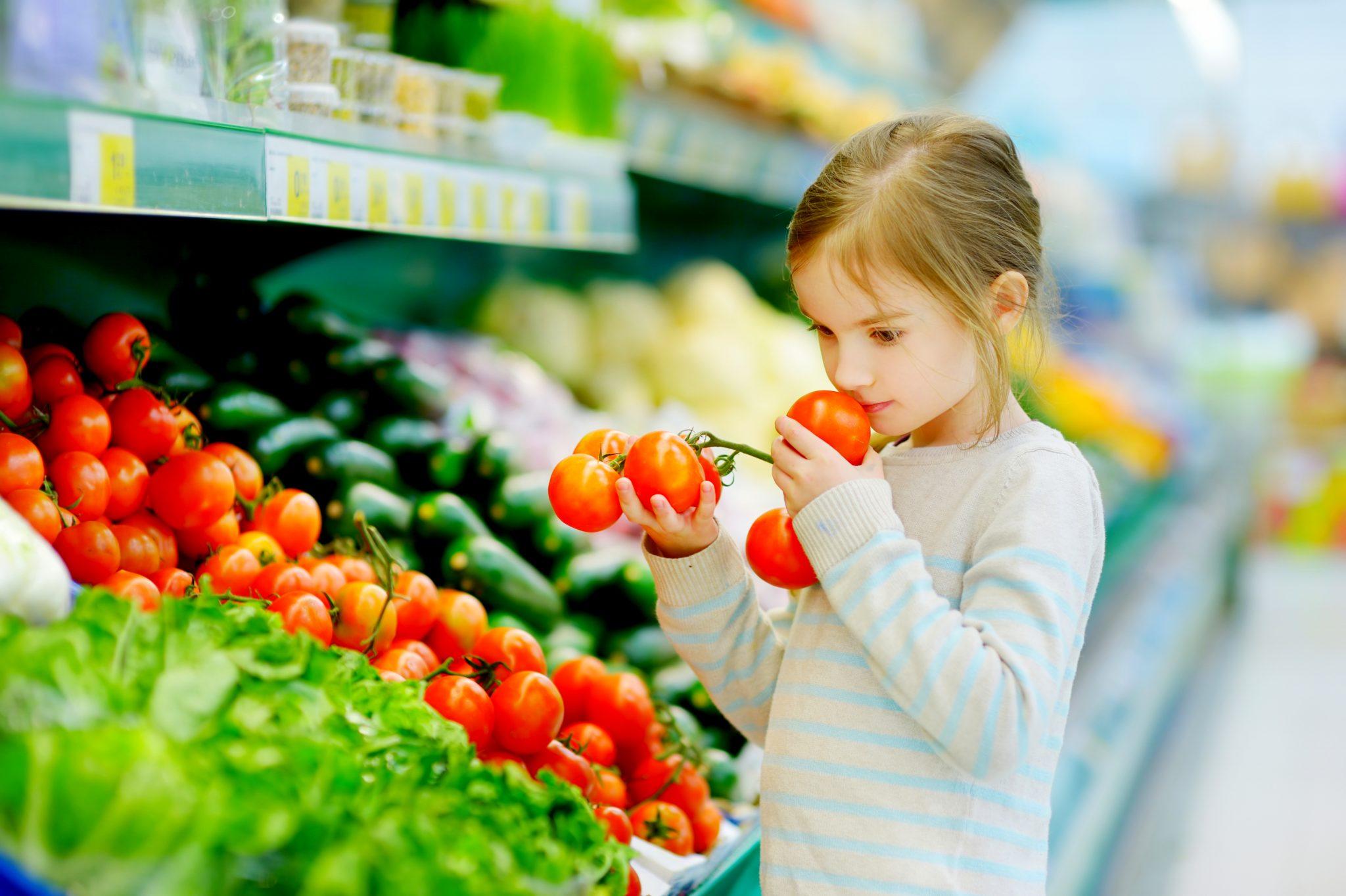 スーパーでトマトを選んでいる女の子