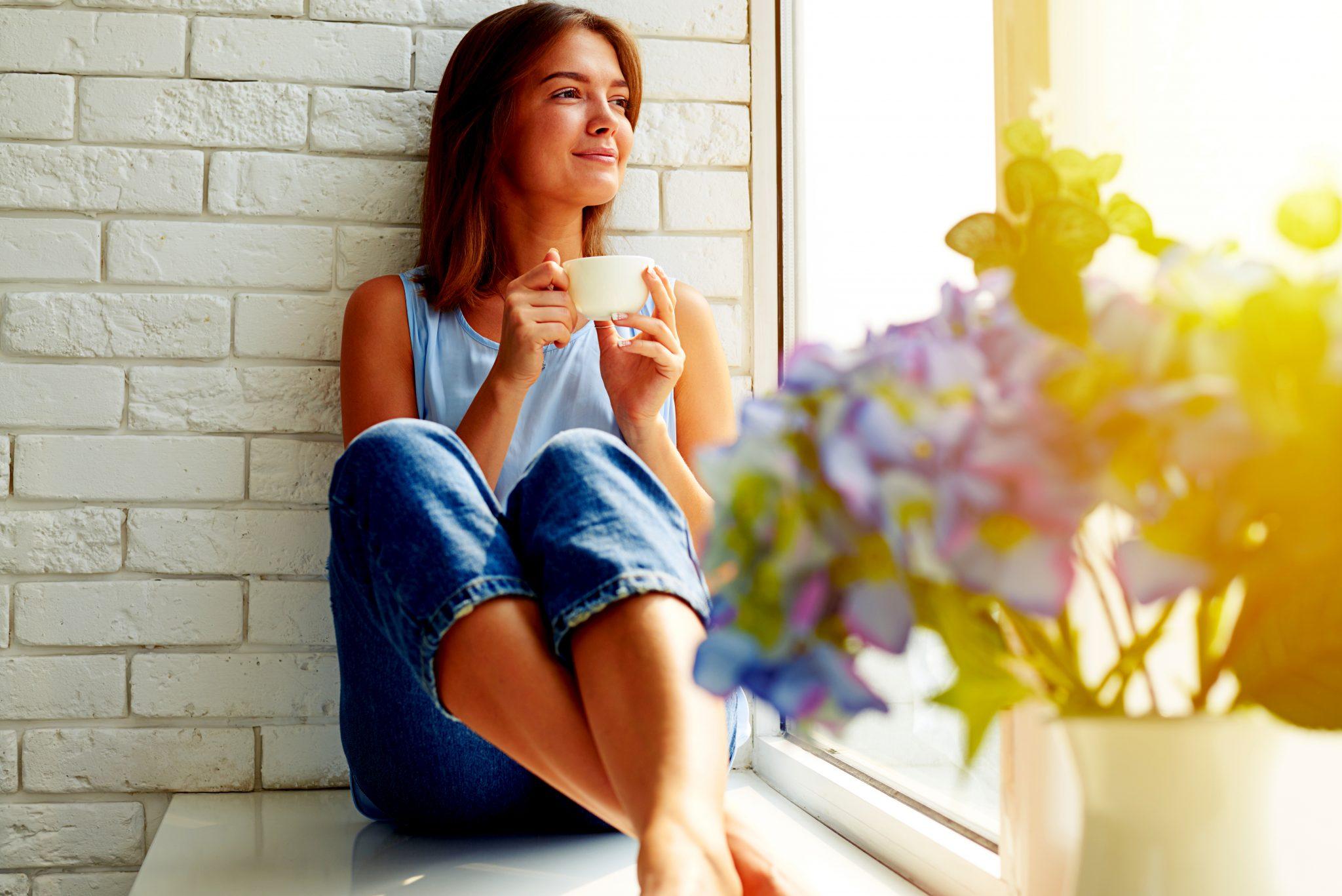 窓際でお茶を飲みながらゆったりしている女性
