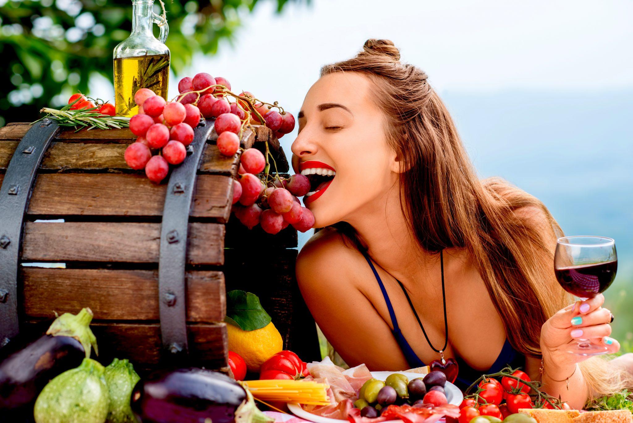 赤ワインを飲みながらブドウを食べている女性