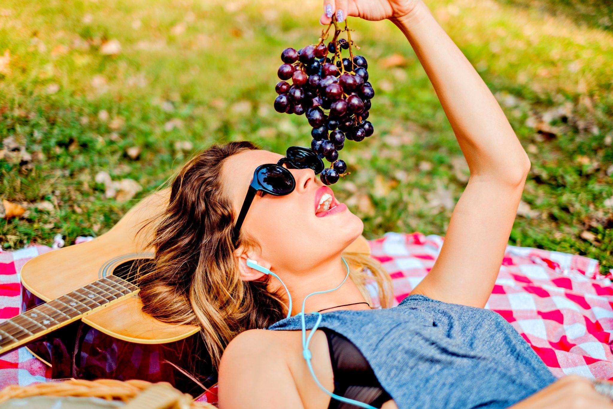 ぶどうを横になりながら外で食べている女性