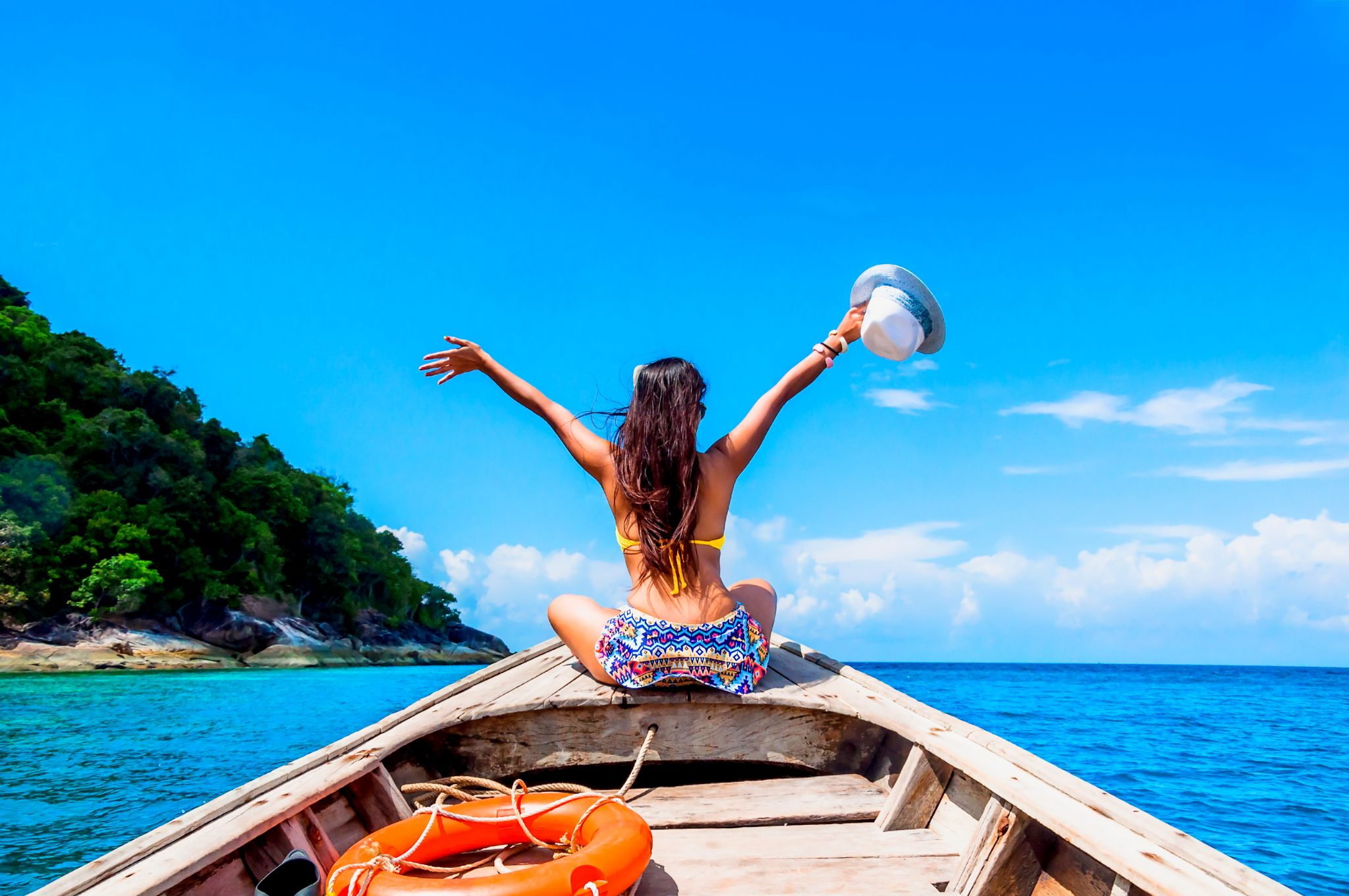 肌のきれいな女性がリゾートビーチでボートに乗っている