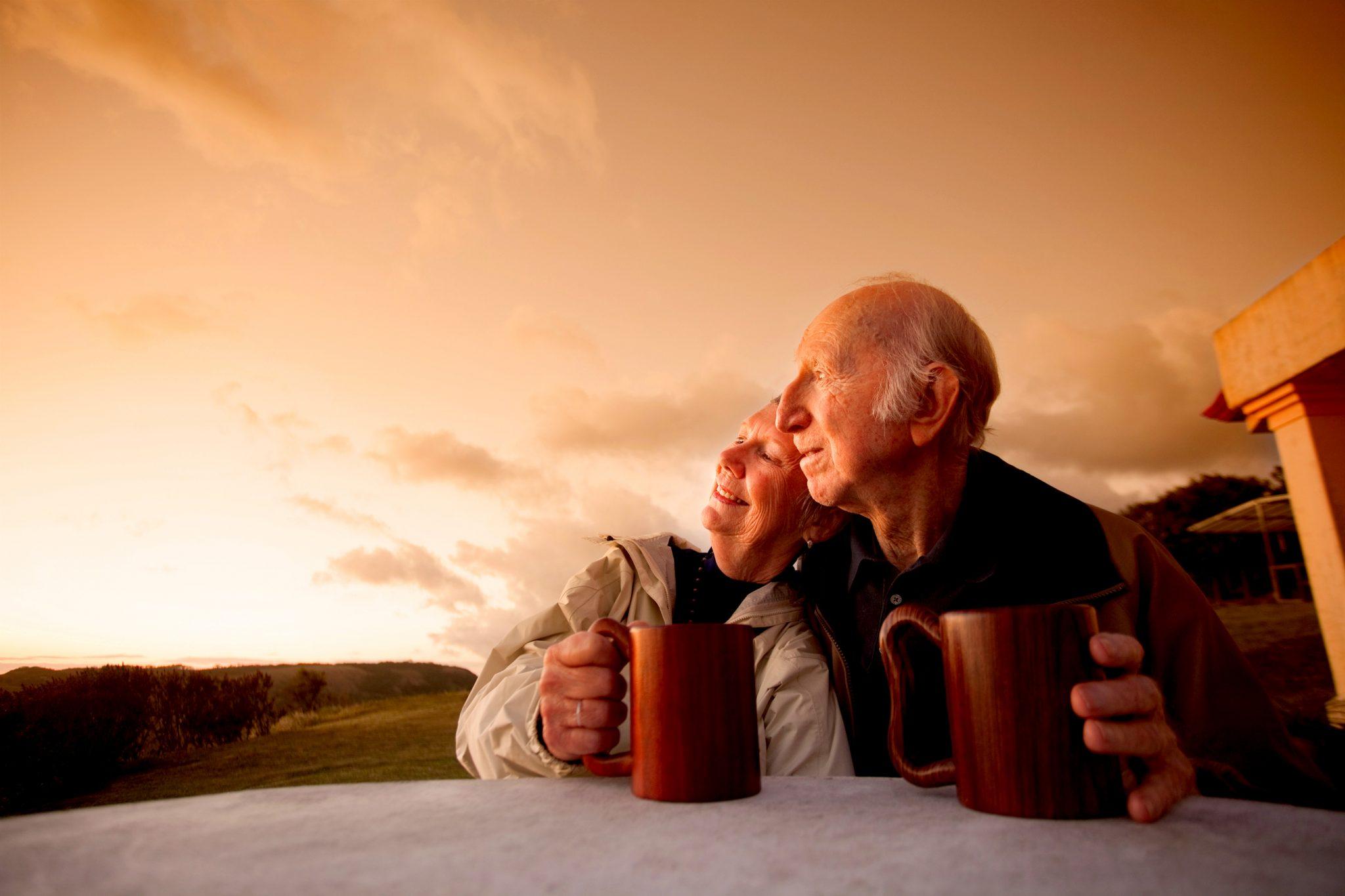 老夫婦が外で仲良くコーヒーを飲んでリラックスしている