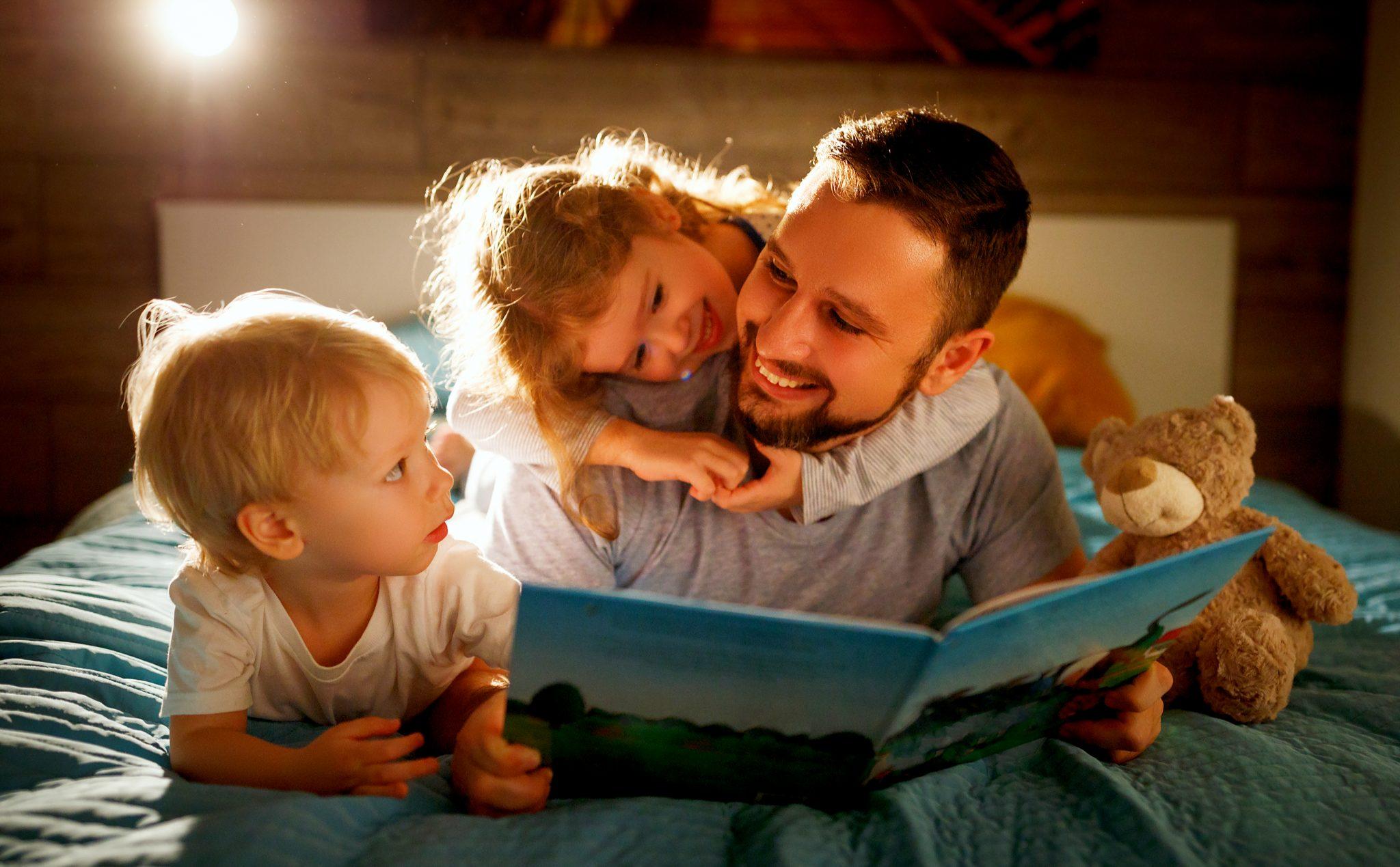 寝る前に息子と娘に本を読んであげているお父さん