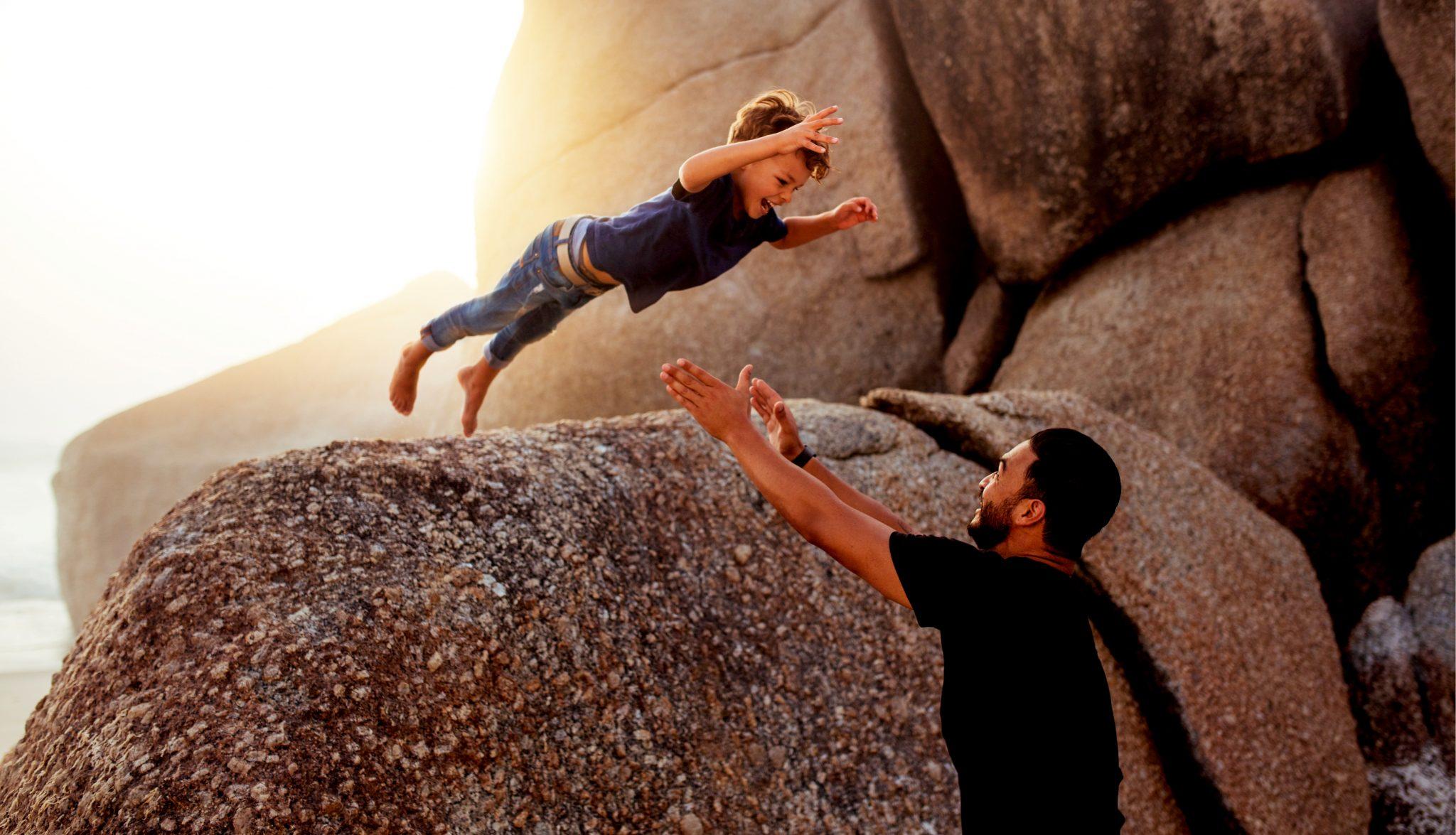 息子が岩からジャンプしているのをパパがキャッチしようとしている