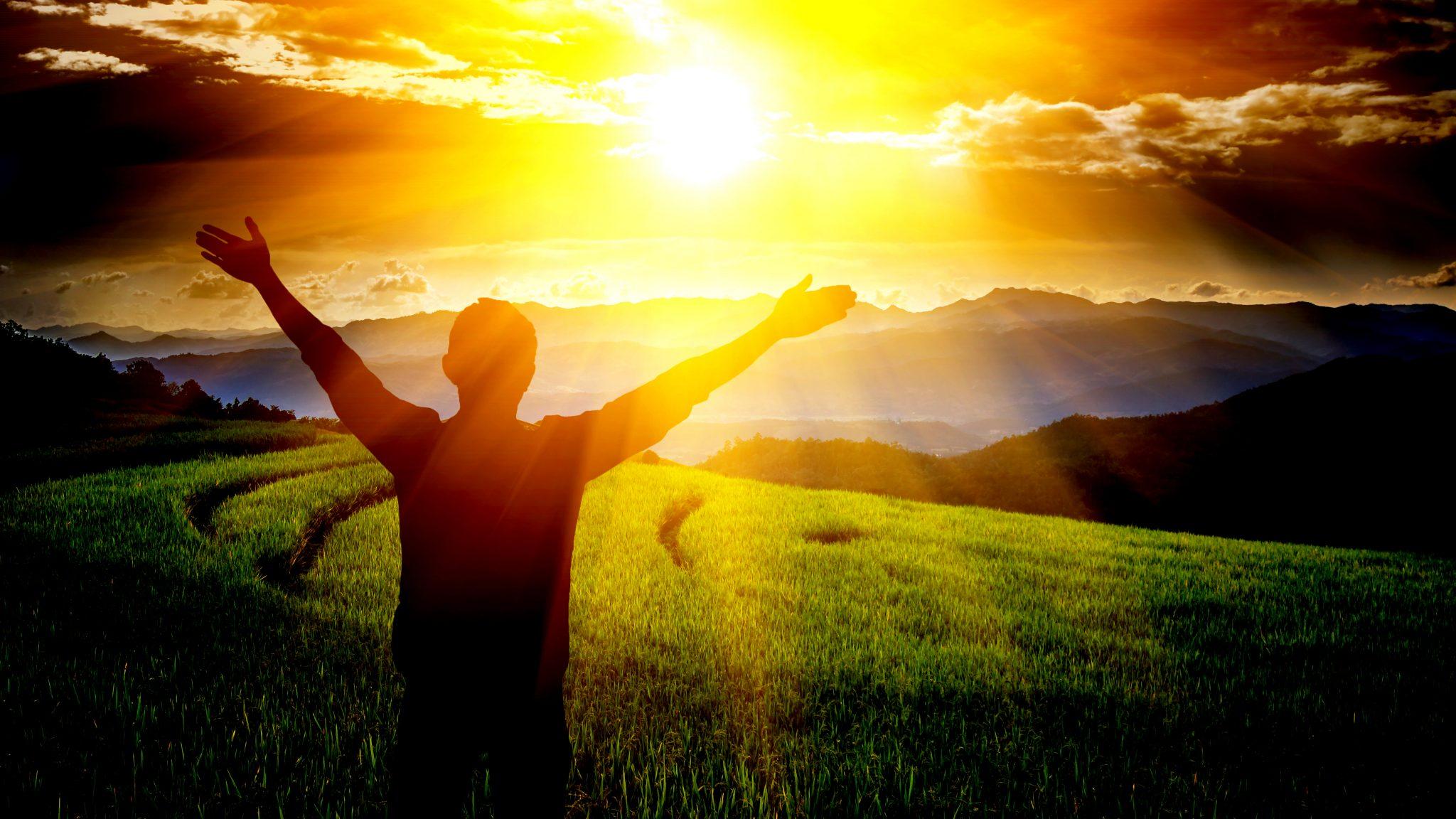 絶景の草原の前で両手を挙げている人