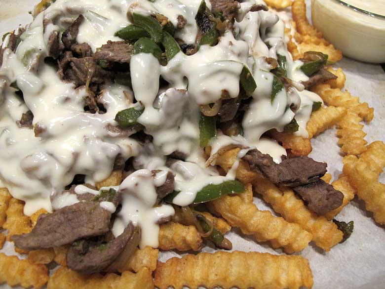 Philly Cheesesteak Fries | eatatkates.com - A savory steak, pepper, & onion mixture coated in a creamy, cheesy sauce all resting on a mound of crispy crinkle-cut fries. Philly Cheesesteak Fries can shared with friends at your Super Bowl gathering or, if you're like me, just make them for dinner.