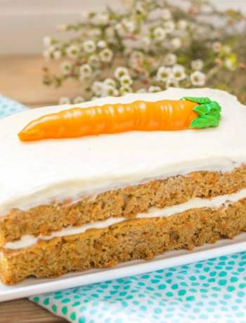 Whole Gluten free carrot cake on platter with flowers