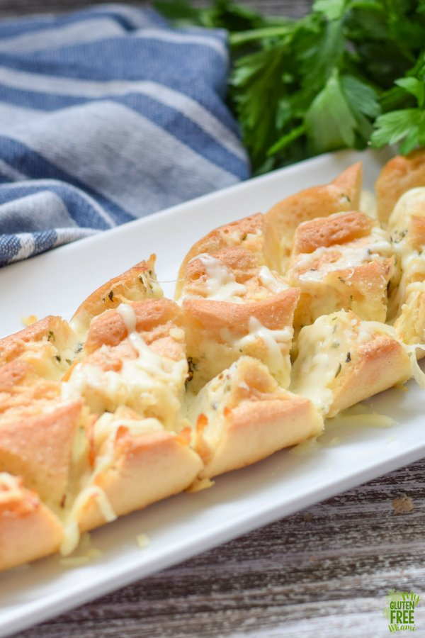 gluten free pull apart cheesy bread on a white tray