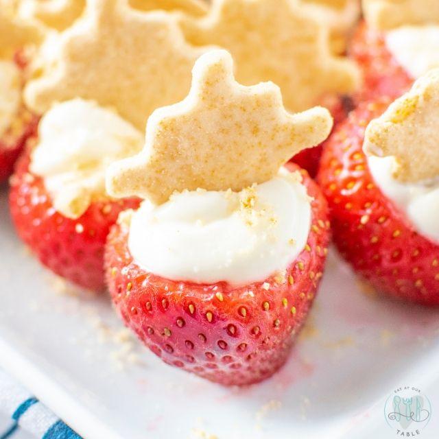 close up of gluten free cheesecake stuffed strawberry with gluten free honey graham snacker
