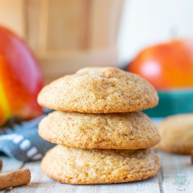 Stack of gluten free apple spice snickerdoodles with cinnamon sticks and apples