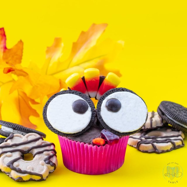 single gluten free thanksgiving turkey cupcake with chocolate creme cookie eyes and fudge striped cookie feather