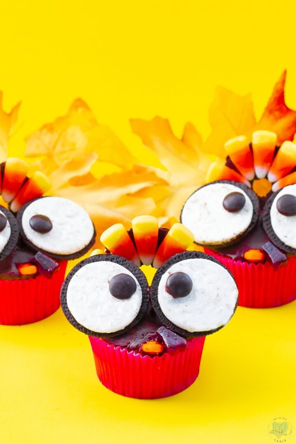 3 gluten free thanksgiving turkey cupcakes on a yellow background with cookie eyes