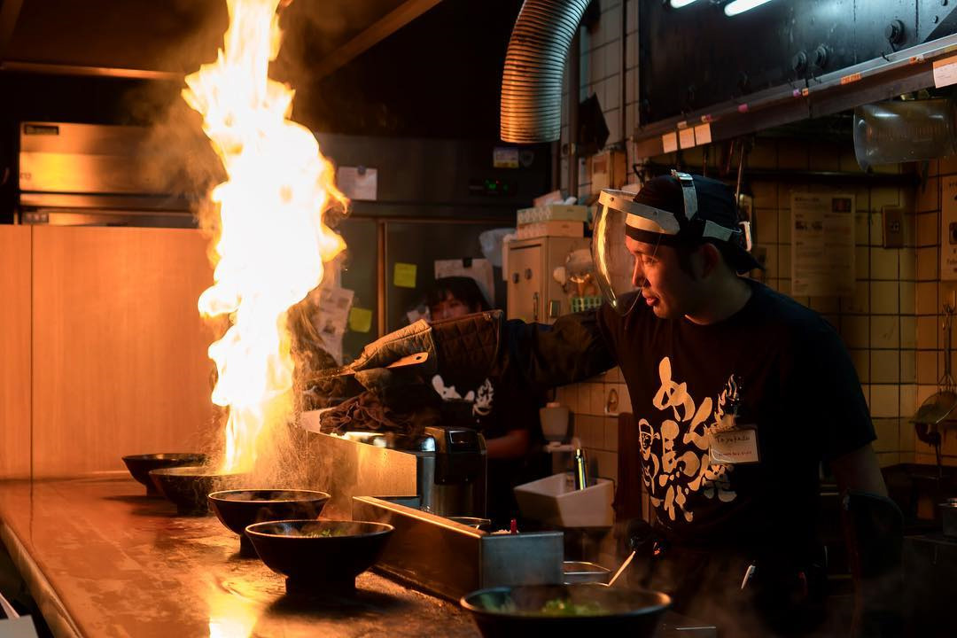 Menbaka Fire Ramen - Chef pouring oil on ramen