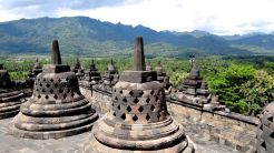 Buddha statues sit inside their burial mounds on the top level of Borobodur