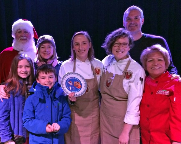 Winners of The Spectacular Cookie Smackdown, Ellie's Bakery. Holding trophy is Ellie's baker Danielle Lowe, to her left is owner Ellen Slattery with her two children (and Santa!), to the right are Pastry Chef Melissa Denmark and judges Chefs Andrew Shotts and Maria Meza