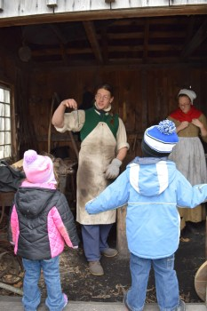 Casey Duckett, assistant director at Coggeshall Farm Museum, demonstrates blacksmithing to young visitors at this living history museum in Bristol, RI.