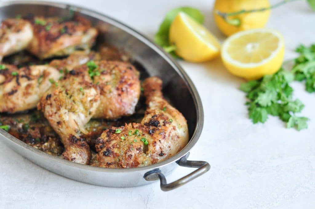 grilled thai chicken thighs in roasting pan with lemon wedges