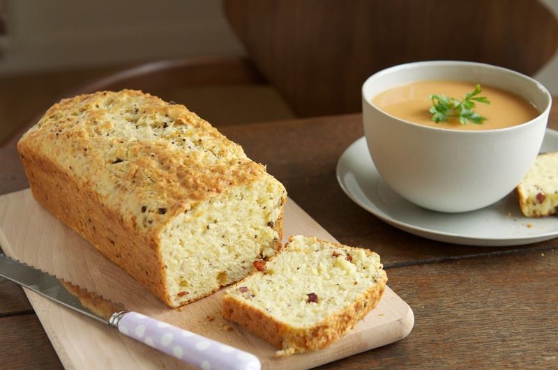 bacon and cheese savoury cake on wooden board with bowl of soup