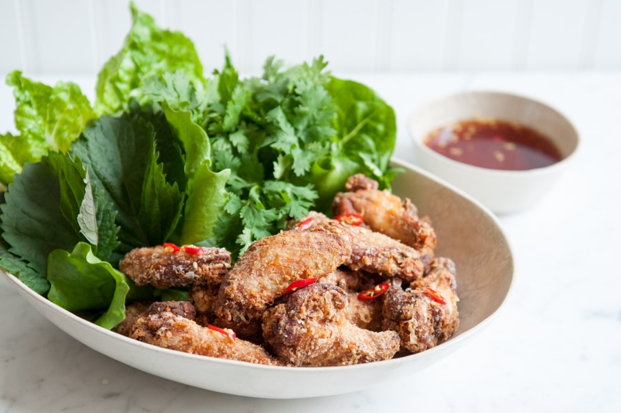 crispy chicken wings with fish sauce in bowl with salad