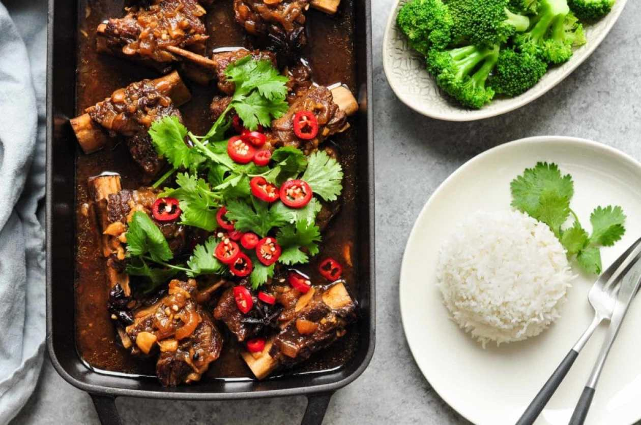 beef short ribs with cilantro and sliced chillies in black roasting tray