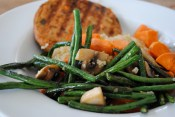 Quinoa topped with a veggie patty, sweet potatoes, and sauteed green beans and mushrooms