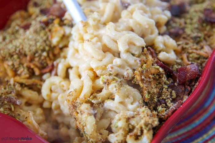 A close up of a dish of food with Cheese, macaroni and Pistachio