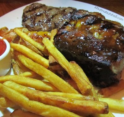 A sandwich and fries on a plate, with Steak and Ribs