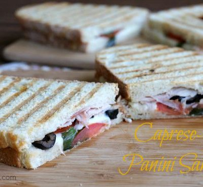 A cut in half sandwich sitting on top of a wooden cutting board, with Ham and Panini