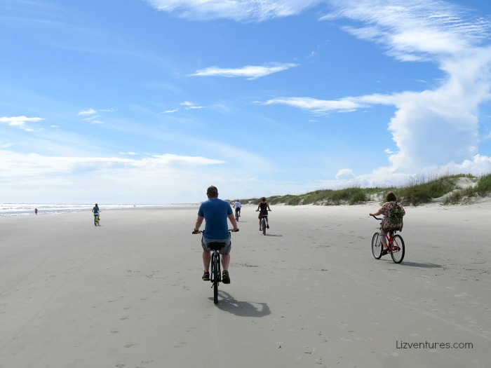 A group of people riding bikes on a sandy beach