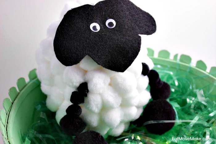A close up of a pom pom sheep stuffed animal